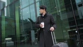 Το κορεατικό άτομο πίνει τον καφέ που στέκεται κοντά στα oudoors αερολιμένων απόθεμα βίντεο