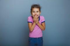 Το κοριτσάκι δίνει ουπς στο στόμα στο γκρίζο υπόβαθρο Στοκ Εικόνα