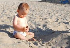 Το κοριτσάκι ανακαλύπτει το κοχύλι στην παραλία Στοκ εικόνα με δικαίωμα ελεύθερης χρήσης