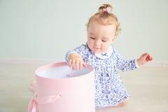 Το κοριτσάκι ανοίγει το δώρο ρόδινο κιβώτιο με το τόξο στοκ εικόνες με δικαίωμα ελεύθερης χρήσης