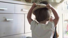 Το κοριτσάκι βάζει στο καπέλο και χαμογελά παίζοντας με τη μητέρα στο σπίτι απόθεμα βίντεο