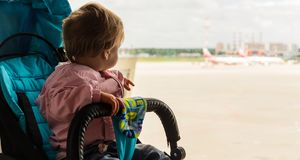 Το κοριτσάκι εξετάζει έξω το παράθυρο τον αερολιμένα στοκ φωτογραφίες με δικαίωμα ελεύθερης χρήσης