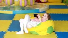 Το κοριτσάκι εξετάζει το κινητό τηλέφωνο Το παιδί παίζει στο smartphone απόθεμα βίντεο