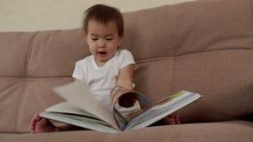 Το κοριτσάκι κάθεται σε έναν μαλακό καναπέ και τα γέλια, που γυρίζουν τις σελίδες ενός ζωηρόχρωμου βιβλίου απόθεμα βίντεο