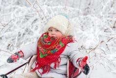 Το κοριτσάκι κάθεται σε ένα έλκηθρο snowdrift μια σαφή χειμερινή ημέρα στοκ φωτογραφία με δικαίωμα ελεύθερης χρήσης