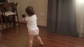 Το κοριτσάκι κρατά μια στήλη μουσικής και περπατά στο πάτωμα σε σε αργή κίνηση και το χαμόγελο απόθεμα βίντεο