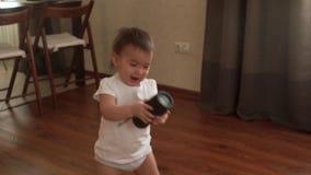 Το κοριτσάκι κρατά μια στήλη μουσικής και περπατά στο πάτωμα σε σε αργή κίνηση φιλμ μικρού μήκους