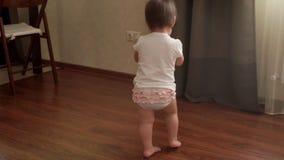 Το κοριτσάκι κρατά μια φορητή στήλη μουσικής και περπατά στο πάτωμα σε σε αργή κίνηση απόθεμα βίντεο