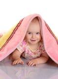 Το κοριτσάκι κρύβει κάτω από το κάλυμμα πέρα από την άσπρη ανασκόπηση στοκ εικόνα