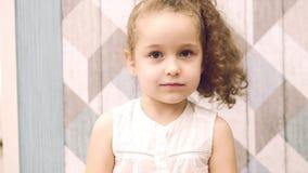 Το κοριτσάκι σε ένα άσπρο φόρεμα και μια σγουρή τρίχα, εξετάζει τη κάμερα, χαμογελά γλυκά και είναι μια μικρή ρίψη Παιδί, παιδιά απόθεμα βίντεο