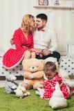 Το κοριτσάκι σε ένα κόκκινο φόρεμα κάθεται σε μια κουβέρτα με τα παιχνίδια βελούδου στο δωμάτιο στα πλαίσια των γονέων της στο κρ Στοκ Εικόνα