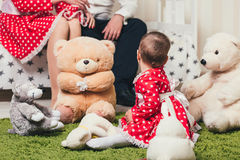 Το κοριτσάκι σε ένα κόκκινο φόρεμα κάθεται σε μια κουβέρτα με τα παιχνίδια βελούδου στο δωμάτιο στα πλαίσια των γονέων της στο κρ Στοκ Φωτογραφία