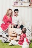 Το κοριτσάκι σε ένα κόκκινο φόρεμα κάθεται σε μια κουβέρτα με τα παιχνίδια βελούδου στο δωμάτιο στα πλαίσια των γονέων της στο κρ Στοκ Φωτογραφίες