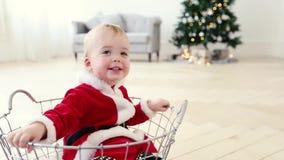 Το κοστούμι santa μωρών κάθεται στο καλάθι με το χριστουγεννιάτικο δέντρο φιλμ μικρού μήκους