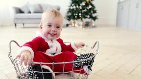 Το κοστούμι santa μωρών κάθεται στο καλάθι με το χριστουγεννιάτικο δέντρο απόθεμα βίντεο