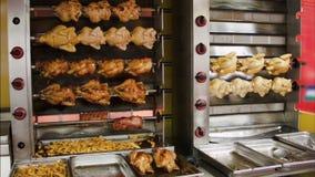 Το κοτόπουλο που τηγανίζεται σε μια μηχανή σχαρών απόθεμα βίντεο
