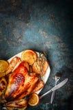 Το κοτόπουλο ψητού στη πιατέλα και οι ψημένες πορτοκαλιές φέτες εξυπηρέτησαν με το δίκρανο και το μαχαίρι στο αγροτικό υπόβαθρο Στοκ φωτογραφία με δικαίωμα ελεύθερης χρήσης