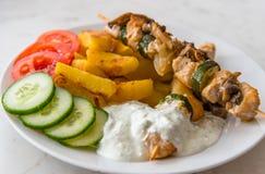 Το κοτόπουλο shish kebab εξυπηρέτησε με τα αμερικανικά potatos, το αγγούρι, τις ντομάτες και το tzatziki Στοκ φωτογραφία με δικαίωμα ελεύθερης χρήσης