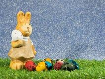 Το κουνέλι Πάσχας στέκεται εκτός από ζωηρόχρωμο των αυγών Πάσχας στην πράσινη χλόη Έννοια ημέρας Πάσχας Διάστημα αντιγράφων για τ Στοκ Εικόνες