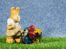 Το κουνέλι Πάσχας στέκεται εκτός από ζωηρόχρωμο των αυγών Πάσχας στην πράσινη χλόη Έννοια ημέρας Πάσχας Διάστημα αντιγράφων για τ Στοκ Εικόνα