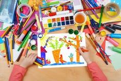 Το κουνέλι σχεδίων παιδιών με το καρότο επάνω κοντά στο σπίτι, τοπ χέρια άποψης με την εικόνα ζωγραφικής μολυβιών σε χαρτί, έργο  Στοκ εικόνα με δικαίωμα ελεύθερης χρήσης