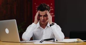 Το κουρασμένο άτομο βγάζει τα γυαλιά του μετά από να εργαστεί στο lap-top φιλμ μικρού μήκους