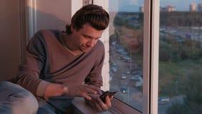 Το κουρασμένο άτομο εξετάζει το κινητό τηλέφωνο, κτυπώντας την ταινία στα κοινωνικά δίκτυα καθμένος στο μπαλκόνι με την άποψη πόλ απόθεμα βίντεο