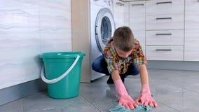 Το κουρασμένο αγόρι στα λαστιχένια γάντια δεν θέλει να πλύνει το πάτωμα στην κουζίνα Εγχώρια καθήκοντα παιδιού απόθεμα βίντεο