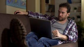 Το κουρασμένο ενήλικο αρσενικό στον καναπέ που εξετάζει το lap-top συγκεντρώθηκε, συνεχής αναζήτηση εργασίας στοκ εικόνα