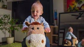 Το κουρασμένο μικρό παιδί χαμογελά οδηγώντας ένα άλογο βελούδου απόθεμα βίντεο