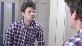Το κουρασμένο νυσταλέο ξυπνημένο άτομο με μια απόλυση στο λουτρό, εξετάζει τον καθρέφτη και προσπαθεί ξυπνήστε φιλμ μικρού μήκους