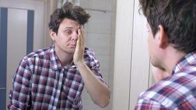 Το κουρασμένο νυσταλέο ξυπνημένο άτομο με μια απόλυση στο λουτρό, εξετάζει τον καθρέφτη και τακτοποιείται απόθεμα βίντεο