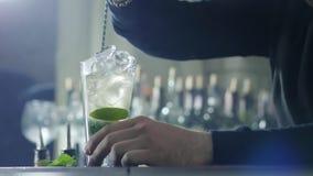Το κουτάλι φραγμών στα χέρια του ατόμου με το ασημένιο βραχιόλι αναμιγνύει το κοκτέιλ με τον πάγο και τα πράσινα φύλλα μεντών στο απόθεμα βίντεο