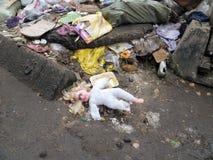 Το κούκλα-κορίτσι με τη χρυσή τρίχα βρίσκεται μεταξύ των συντριμμιών στην περιβολή Στοκ εικόνες με δικαίωμα ελεύθερης χρήσης