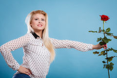 Το κράτημα γυναικών κόκκινο αυξήθηκε λουλούδι στο μπλε Στοκ φωτογραφία με δικαίωμα ελεύθερης χρήσης
