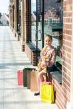 Το κράτημα κοριτσιών teddy αντέχουν και το κάθισμα στην προθήκη με τις τσάντες αγορών Στοκ Εικόνες