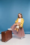 Το κράτημα μικρών κοριτσιών teddy αντέχουν και η τοποθέτηση με τη βαλίτσα στο στούντιο Στοκ Εικόνες