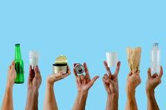 Το κράτημα χεριών και παρουσιάζει ανακύκλωσης υλικά στο μπλε υπόβαθρο στοκ φωτογραφία με δικαίωμα ελεύθερης χρήσης