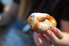 Το κράτημα χεριών doughnut που ξεσκονίστηκε με την κονιοποιημένη ζάχαρη κοντά επάνω Στοκ Εικόνες