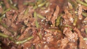 Το κρέας βόειου κρέατος είναι τηγανισμένο στο τηγάνισμα του τηγανιού με τα κρεμμύδια και τα πράσινα φασόλια Κρέας προετοιμασιών φιλμ μικρού μήκους