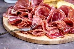 Το κρέας δίσκων τροφίμων με τα εύγευστα κομμάτια σαλαμιού του τεμαχισμένων ζαμπόν και των κροτίδων και ραβδιών ψωμιού καλύπτει κο Στοκ εικόνα με δικαίωμα ελεύθερης χρήσης