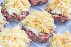 Το κρέας συσσωρεύει ακατέργαστα φρέσκα cutlets χοιρινού κρέατος με τα τηγανισμένα κρεμμύδια και τα βρασμένα αυγά και τις πατάτες  στοκ εικόνες