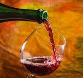 Το κρασί χύνει στο γυαλί του μπουκαλιού Στοκ Φωτογραφία