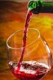 Το κρασί χύνει στο γυαλί του μπουκαλιού Στοκ Εικόνες