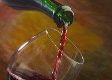 Το κρασί χύνει στο γυαλί του μπουκαλιού Στοκ εικόνα με δικαίωμα ελεύθερης χρήσης