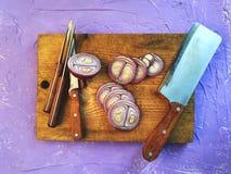 Το κρεμμύδι είναι ολόκληρο και τεμαχισμένο Τεμαχισμένα κρεμμύδια σε έναν τέμνοντα πίνακα Στοκ Φωτογραφίες