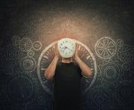 Το κρύβοντας πρόσωπο τύπων που κρατά ένα ρολόι αντί του κεφαλιού στέκεται πέρα από το σκοτεινό πίνακα με τα συρμένα εργαλεία και  στοκ φωτογραφία