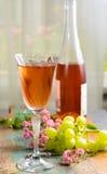Το κρύο καλοκαίρι αυξήθηκε κρασί, που εξυπηρετήθηκε στο όμορφο γυαλί στο πεζούλι στο γ Στοκ φωτογραφία με δικαίωμα ελεύθερης χρήσης
