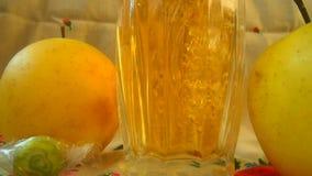 το κρύσταλλο πίνει το γυ& Μήλα κοντά στο ποτήρι του ποτού φρούτων φιλμ μικρού μήκους