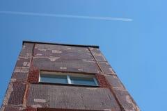 Το κτήριο και το ίχνος αεροπλάνου στον ουρανό Στοκ Εικόνα